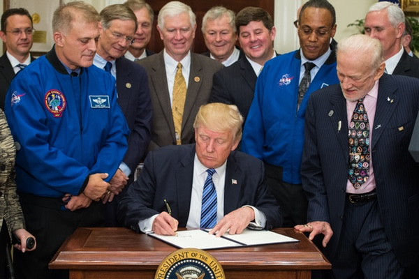 President Donald Trump signs an executive order June 30 formally reestablishing the National Space Council, as astronauts, members of Congress, and industry executives look on. (credit: NASA/Aubrey Gemignani)